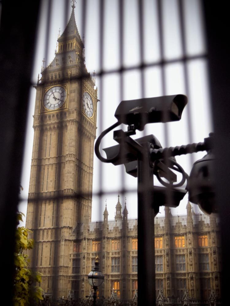 Security camera is monitoring the area behind the bars of the metal fence around Big Ben and The Houses Of Parliament