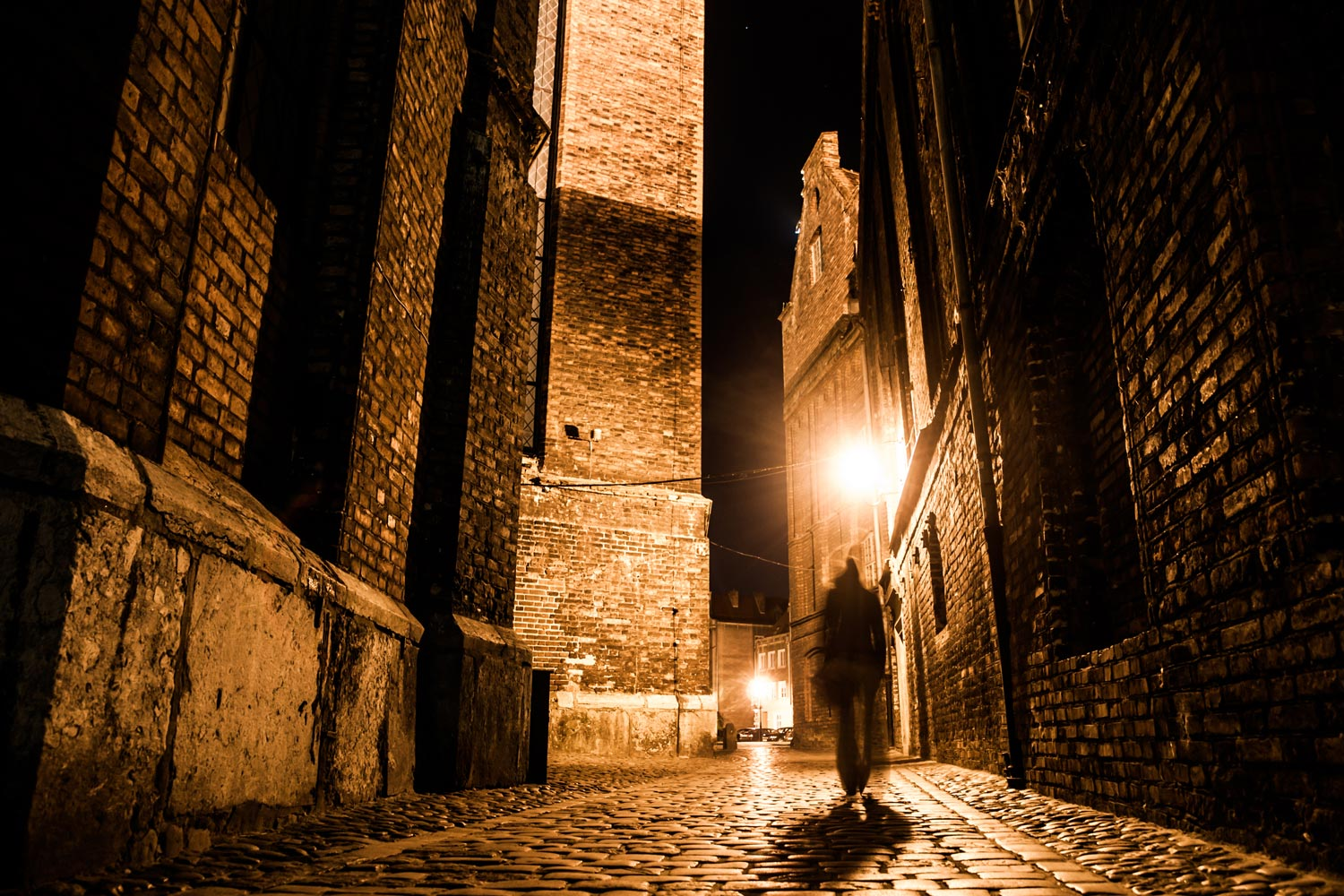 Illuminated cobbled street with light reflections